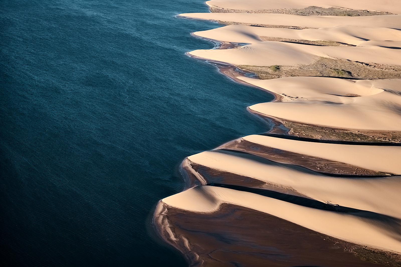 Wüstenlandschaft aus der Vogelperspektive, Wüstendünen in einem Farbspiel aus orange, gold